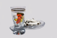 Pills in glass and cigarette butts Royalty Free Stock Images