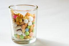 Pills in glass Stock Image