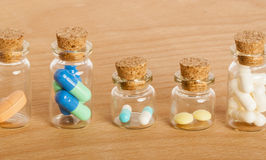 Pills in glass jars. Colourful pills in five glass jars with corks Stock Photo
