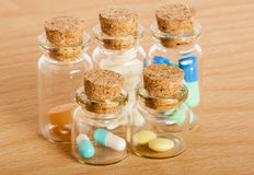 Pills in glass jars. Colourful pills in five glass jars with corks Stock Photography