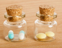 Pills in glass jars. Colourful pills in two glass jars with corks Royalty Free Stock Photography