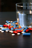 Pills and glass of water Stock Images