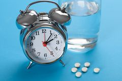 Pills with glass of water and alarm clock Royalty Free Stock Photos