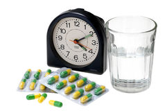 Pills with glass of water and alarm clock Stock Photos