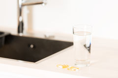 Pills and glass of water on countertop Stock Photo