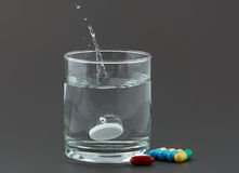 Pills and glass of water on grey background. Closeup of  pills and glass of water on grey background Royalty Free Stock Photos