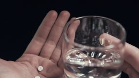 Pills and glass of water in hand isolated black background Man taking pills POV stock video