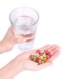 Pills and glass of water in hands Stock Image