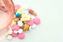 Pills and glass of water on white background Stock Photos