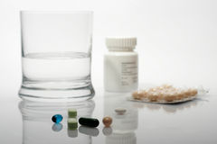 Pills and glass of water Royalty Free Stock Photos