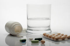 Pills and glass of water Royalty Free Stock Images