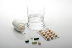 Pills and glass of water. On white background Stock Photography