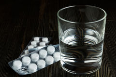 Pills with glass of water Stock Photography