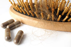 Pills for hair loss treatment and  brush Royalty Free Stock Photo
