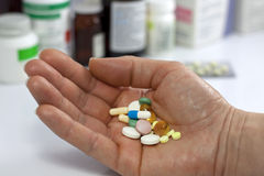 Pills in hand against medicines in pharmacy Royalty Free Stock Images