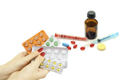 Pills in hand as well as a variety of pharmacological drugs and Stock Photos