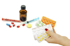 Pills in hand as well as a variety of pharmacological drugs and Royalty Free Stock Photography