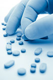 Pills and hand in blue Royalty Free Stock Images