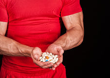 Pills in hand. Different pills and vitamins in strong male hands Royalty Free Stock Images