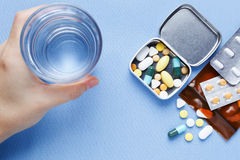 Pills with hand holding drinking water Stock Photos