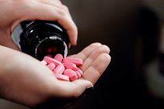 Pills in hand, pink vitamins stock photography