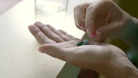 Pills in the Hand. Woman fingering pills in her hand. Young girl taking medicaments stock footage