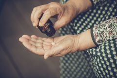 Pills in the hands of an old woman close-up, toned Stock Photos