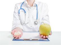 Pills or health food. Doctor offers a choice: pills or health food Stock Photo