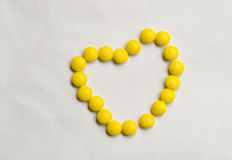 Pills heart. Small yellow pills makes a heart Stock Images