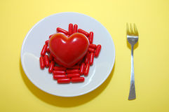 Pills for Heart. Red pills, a red heart on a white plate and a fork on a yellow background Stock Photo