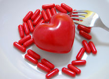 Pills for Heart. Red pills and a red heart on a white plate with a fork Stock Photos