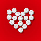 Pills in heart arrange on red background Stock Photography