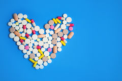 Pills heart on a blue background top view. Stock Images