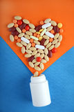 Pills heart with bottle. Pills in shape of love heart on orange and blue background with bottle Stock Image