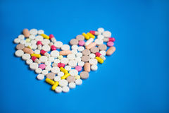 Pills in a heart shape on a blue background. Royalty Free Stock Photo