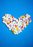 Pills in a heart shape on a blue. Royalty Free Stock Photos