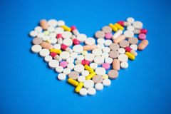 Pills in a heart shape close-up. Royalty Free Stock Photography