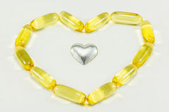 The pills in heart shape and silver heart. Pills in heart shape and silver heart Royalty Free Stock Photos