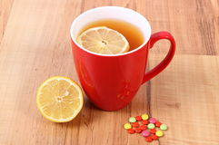 Pills and hot tea with lemon for colds, treatment of flu and runny Royalty Free Stock Image