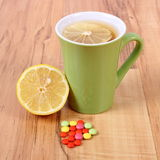 Pills and hot tea with lemon for colds, treatment of flu and runny Royalty Free Stock Photo