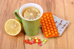 Pills and hot tea with lemon for colds, treatment of flu and runny Stock Photos