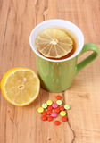 Pills and hot tea with lemon for colds, treatment of flu and runny Royalty Free Stock Images
