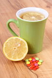 Pills and hot tea with lemon for colds, treatment of flu and runny Stock Photo