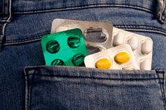 Pills in the jeans pocket. stock photo