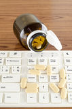 Pills on keyboard computer Stock Images
