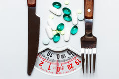 Pills with knife fork on white scales Stock Photo