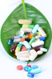 Pills on a leaf. Some pills on a leaf isolated on white Stock Images