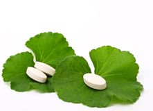 Pills and leaves. Pills of the green leaf. White background royalty free stock images
