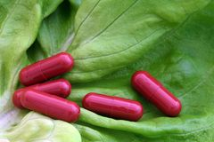 Pills on lettuce leaf. Red pills on a lettuce leaf Stock Photo