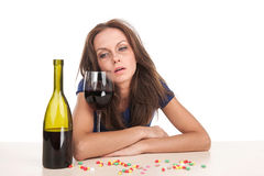 Pills lying on table with bottle of wine on white background. Royalty Free Stock Images